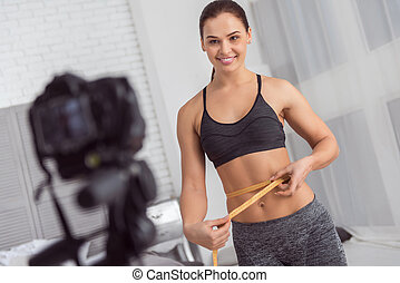 Alert young woman measuring her waist