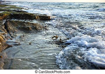 Algae Covered Beach Rocks - Gushing surf of a wave smashing...