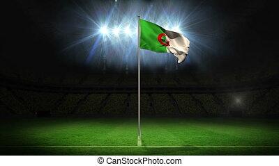 Algeria national flag waving on flagpole on football pitch...
