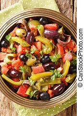Algerian salad Chlada felfel with green pepper tomato, anchovies and mix of olives close-up in a bowl. vertical top view