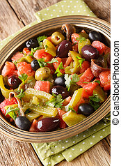 Algerian salad Chlada felfel with green pepper tomato, anchovies and mix of olives close-up in a bowl. vertical