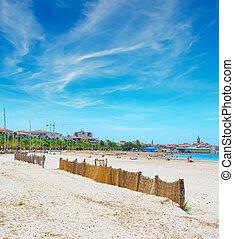 Alghero shoreline under a blue sky with clouds