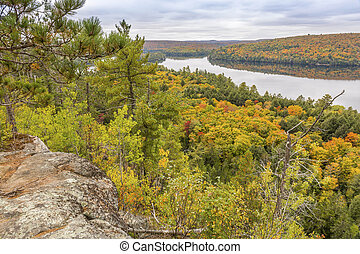 Looking out over a fall forest with a lake in the background - Algonquin Provincial Park, Ontario, Canada