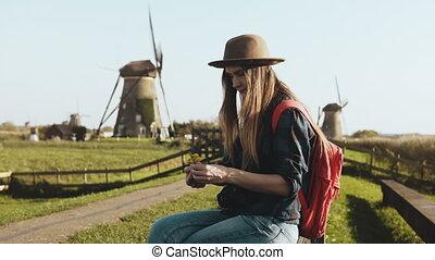 alhier, jonge vrouw , zit, dichtbij, oud, rustiek, mill., cowgirl, in, hoedje, met, langharige, en, rood, schooltas, maakt, een, bloem, bouquet., 4k