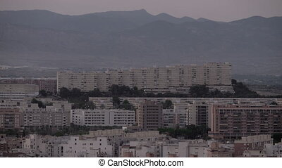Alicante buildings against misty evening mountains - An...