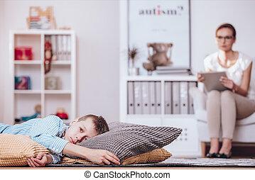 Alienated boy lying on pillows
