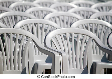 View of some white plastic cafe, restaurant or garden chairs, in an aligned fashion on a outdoor setting.