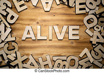 ALIVE word made with block letters lying on wooden board