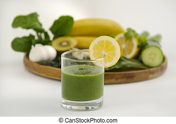 Green smoothie alkaline diet drink with fresh lemon beside a wooden tray with alkaline diet vegetables and fruits: Banana, kiwi, spinach, lemon, cucumber, parsley , silver beat and garlic.