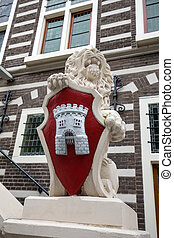 Lion sculpture with coat of arms at Stadthuis, City Hall in...