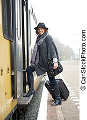 Mature woman with suitcase luggage is boarding the train from the platform and smiling at the camera