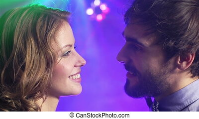 Close-up of a lovely clubbing couple with their eyes glued on each other