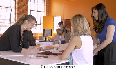 All female small business start up collaborating and working...