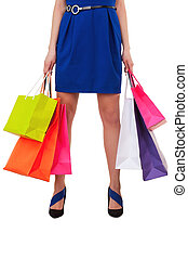 All I got on sale. Close-up of female hand holding multi colored shopping bags