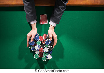 Poker player betting all in and holding a lot of chips stacks, hands close up, top view