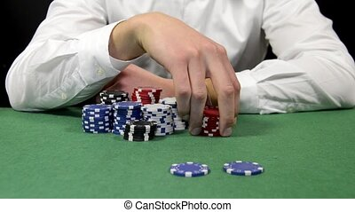 All in - Poker player fiddling contemplative with his chips,...