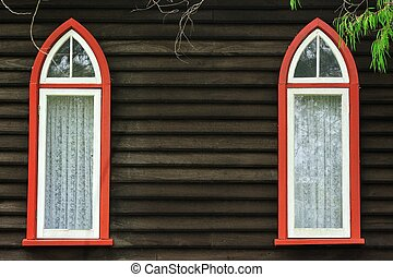 Dark wall of weatherboard church with 2 pointed-arch windows