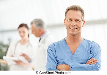 alleen, de, best, medisch, treatment., verticaal, van, een, smart, middelbare leeftijd , mannelijke arts, in, blauw uniform, staand, voor, zijn, collega's, en, het glimlachen