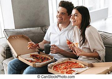 allegro, giovane coppia, seduta, su, uno, divano, a casa