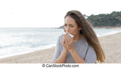 Allergic woman sneezing walking on the beach