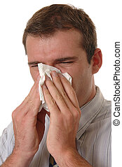 Allergies - A young man with allergies sneezing into a...