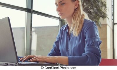 Allergy and health problems for young woman sneezing in office while using laptop computer