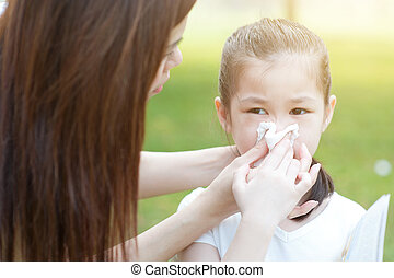 Allergy. Little girl blowing nose.