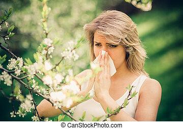 Allergy - Woman with pollen allergy in springtime near tree...