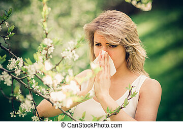 Allergy - Woman with pollen allergy in springtime near tree...