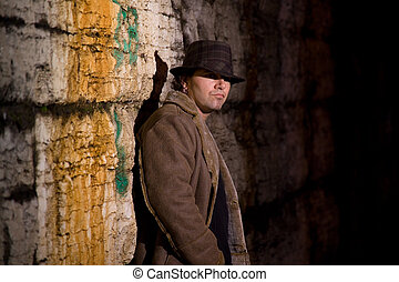 Man with hat and coat in dark alley