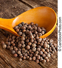 Allspice in the spoon on wooden table