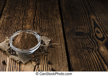 Allspice Powder (close-up shot) on rustic wooden background