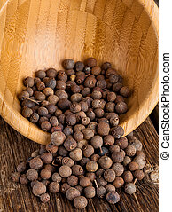 Allspice in the bowl on wooden table