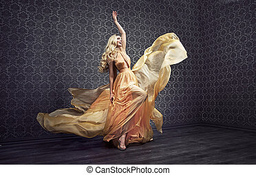 Alluring blond woman dancing in a stylish gown
