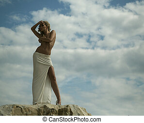 Alluring blond woman over the sky background