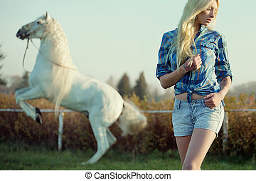 Alluring blonde beauty with majestic horse in the background