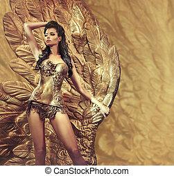 Alluring brunette holding a huge golden wing