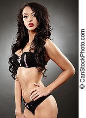 Alluring brunette in black lingerie with hand on hip