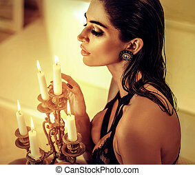Alluring brunette lady holding a candlestick