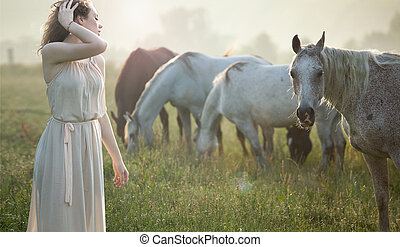 Alluring brunette walking next to the horses