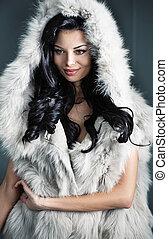 Alluring brunette woman wearing stylish fur coat