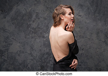 Alluring charming young woman in black dress with open back