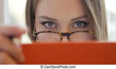 Alluring flirty shy young blonde woman in glasses covered her face by the book close up