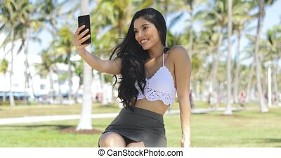 Alluring girl posing for selfie in park - Stylish playful...