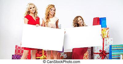 Alluring ladies holding empty billboard