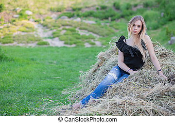 Alluring lady posing sitting on the hay.