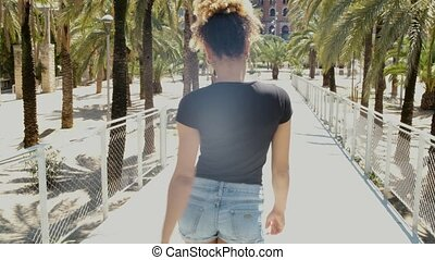 Alluring stylish black woman on street - Crop back view of...