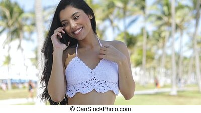 Alluring stylish girl having phone call in park