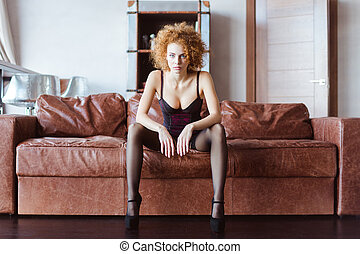 Alluring tender woman in lingerie and stockings posing on sofa