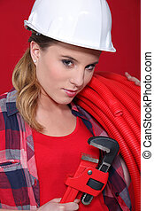 Alluring woman holding corrugated tubing and a pipe wrench